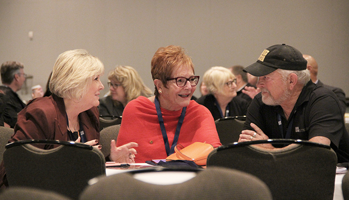 Claudia Vicino, Mary Ann Sanders and Tom Teagle discuss a prompt during a keynote.