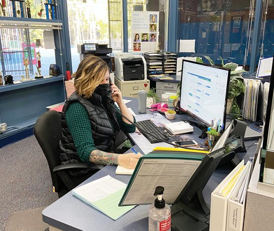 District staff member on the phone at her desk.